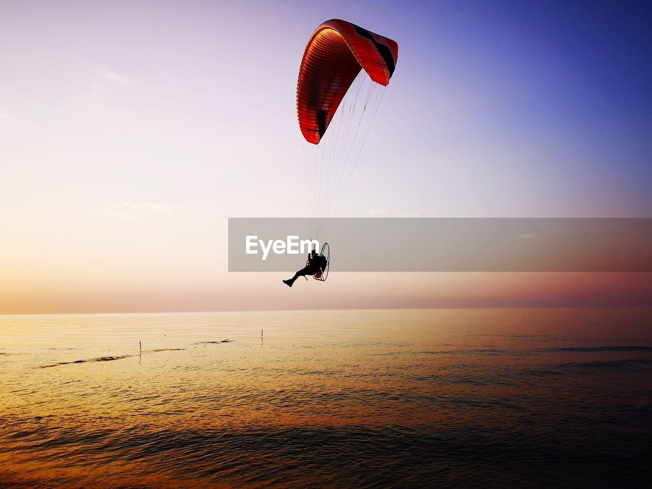 Silhouette Person Paragliding Over Sea Against Sky During Sunset