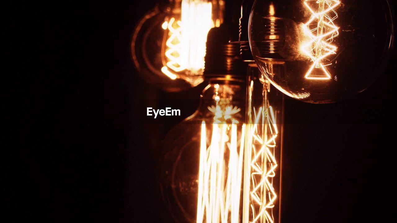 Cropped image of illuminated light bulbs against black background