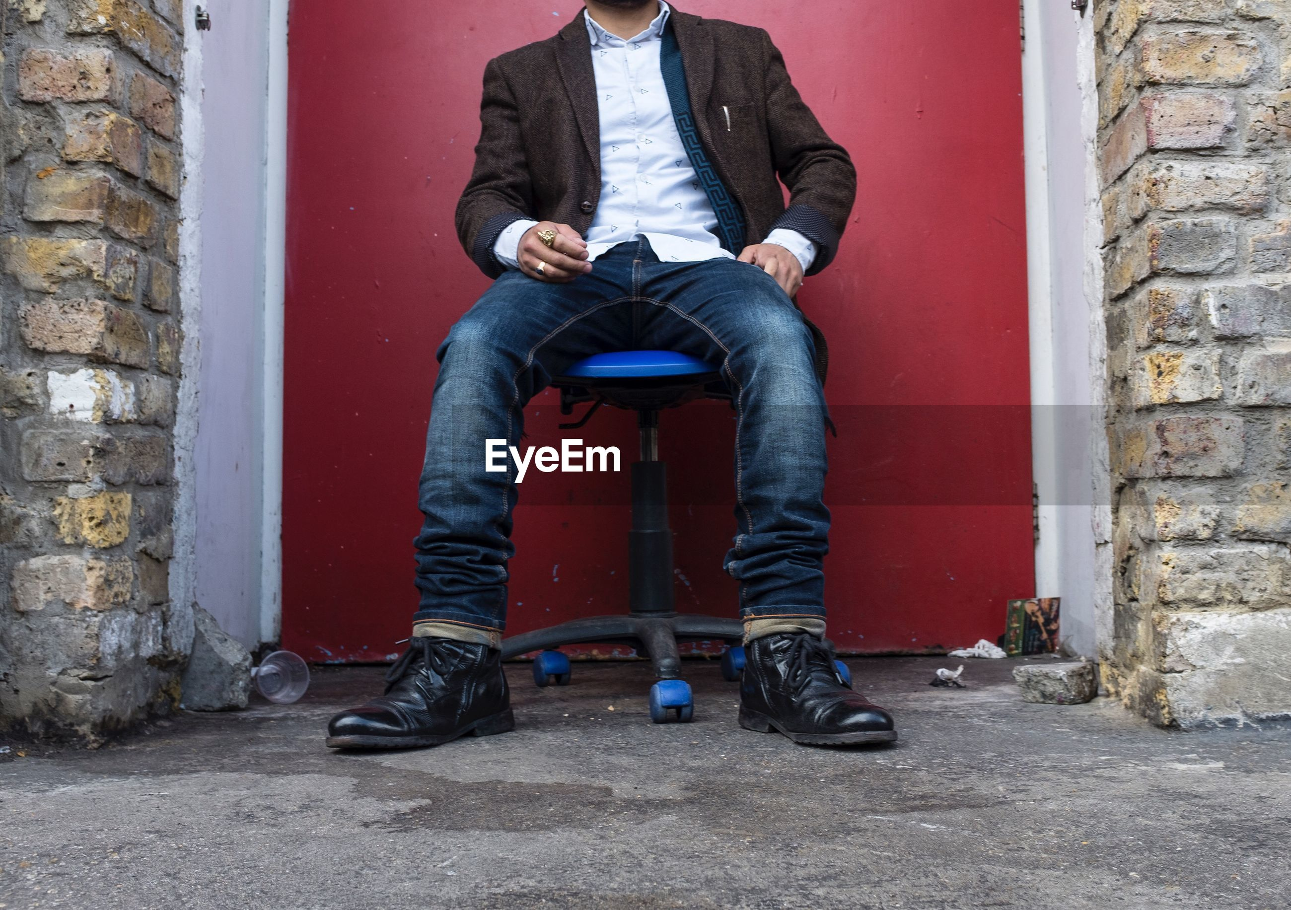 Low section of person sitting on office chair against door