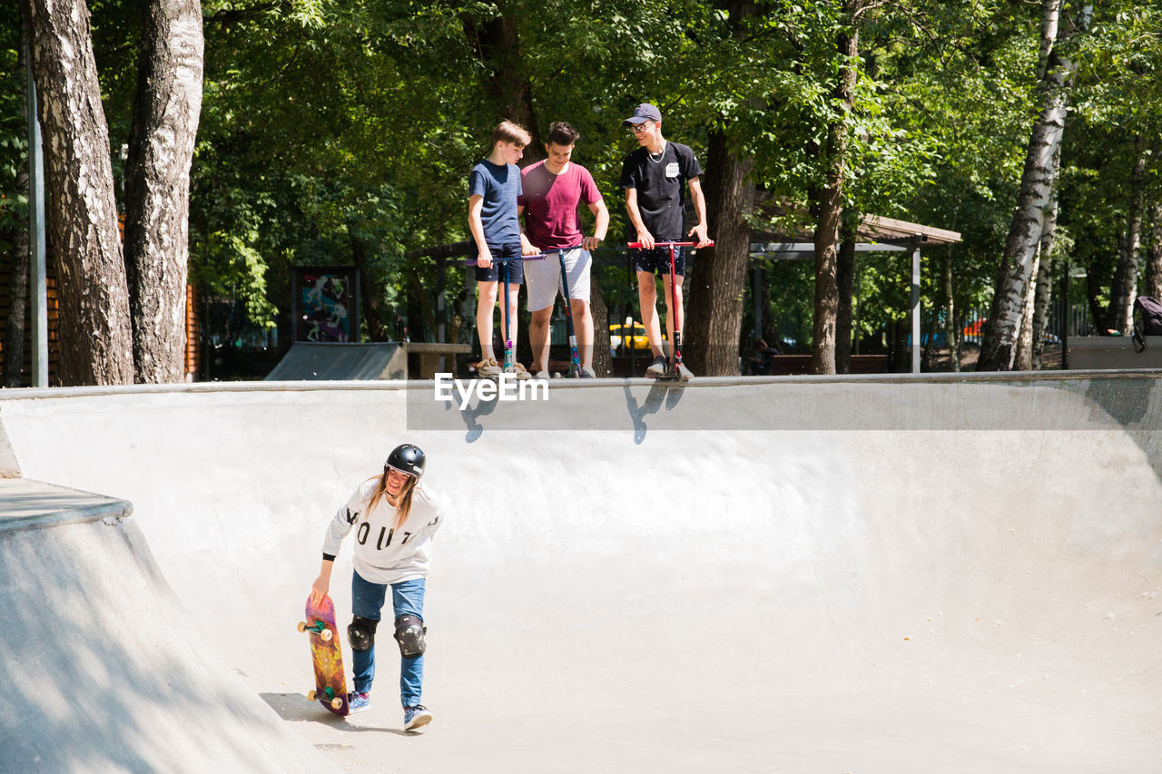 full length, tree, togetherness, child, group of people, casual clothing, men, leisure activity, plant, day, nature, males, boys, real people, people, childhood, lifestyles, friendship, skateboard park, outdoors, teenager, teenage boys, adolescence