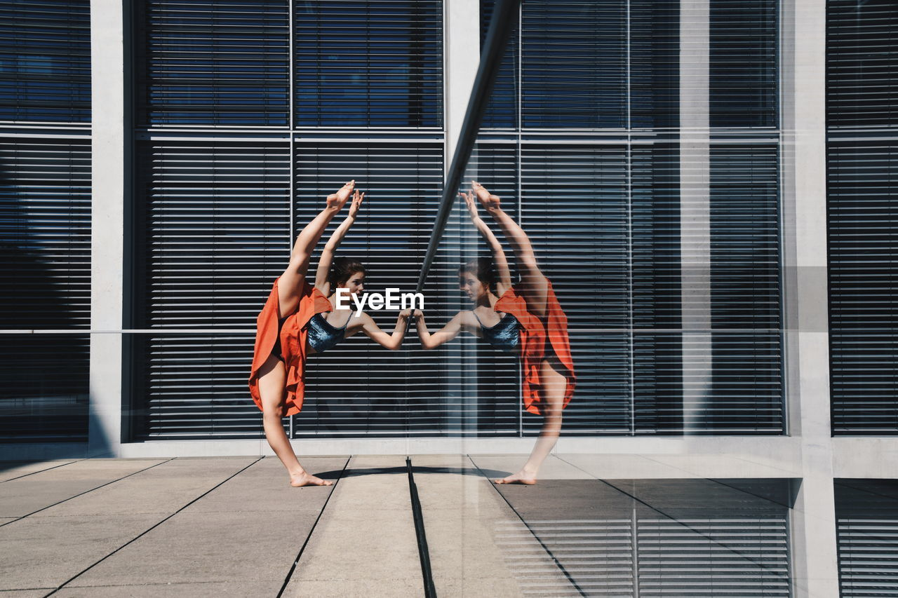 Full length of woman doing gymnastics on floor with reflection in glass window of building