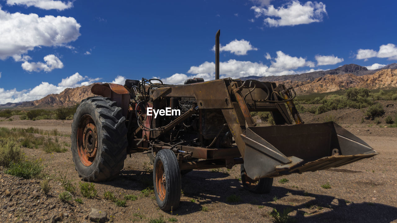 ABANDONED TRUCK ON FIELD AGAINST SKY