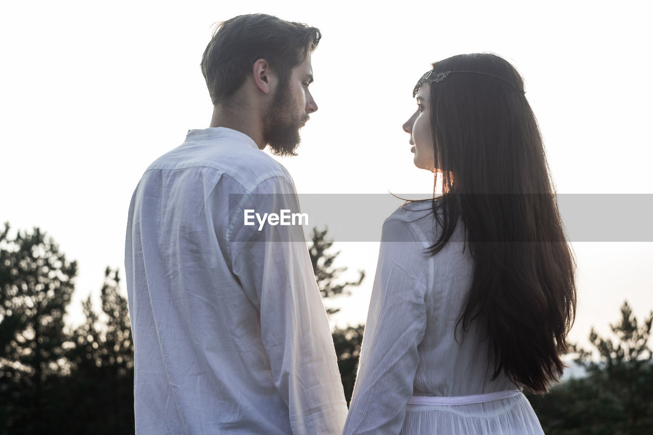 togetherness, young adult, two people, young women, love, bonding, waist up, standing, real people, couple - relationship, young men, emotion, lifestyles, women, positive emotion, casual clothing, people, hair, leisure activity, long hair, hairstyle, outdoors