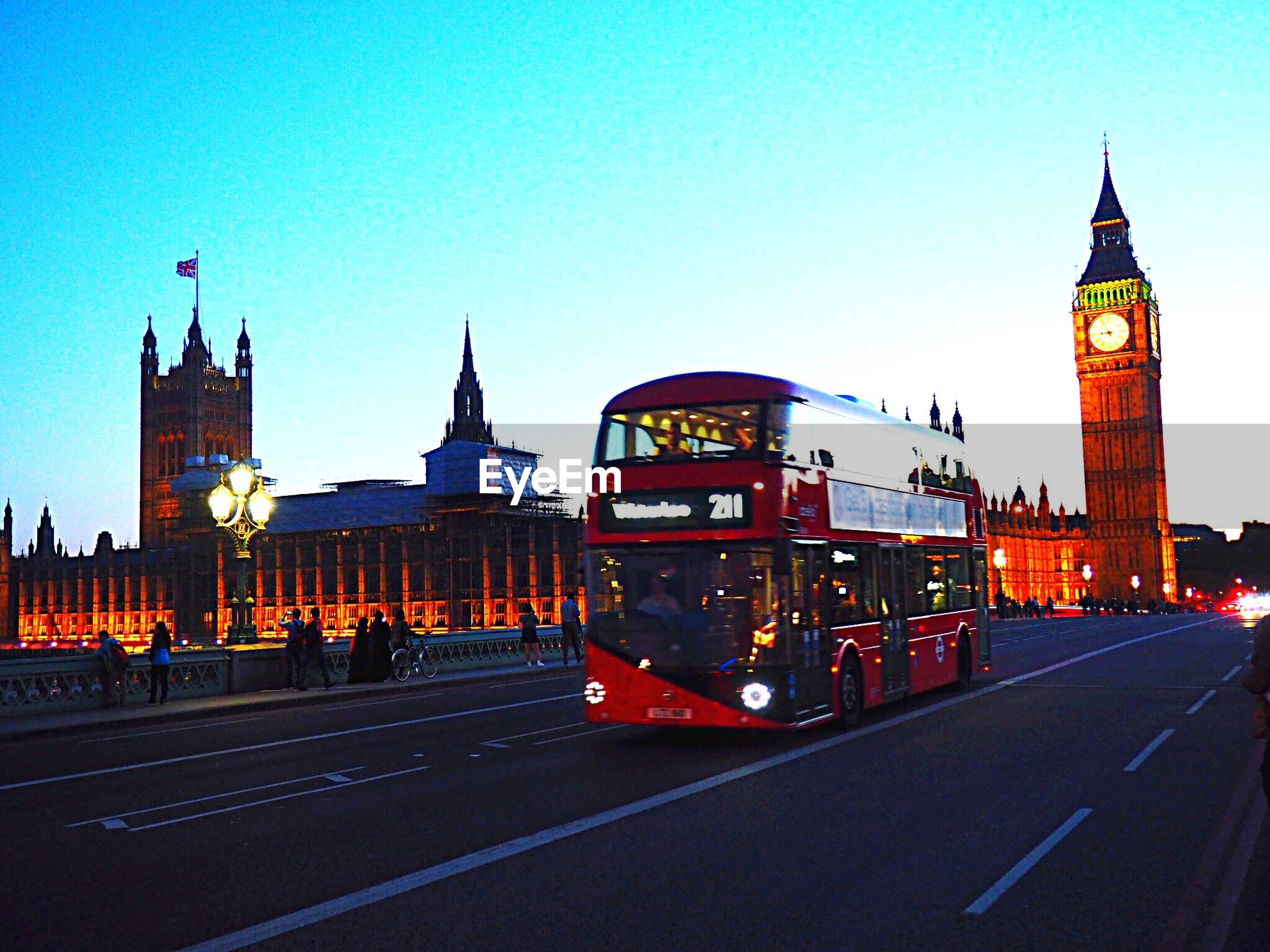 architecture, building exterior, built structure, travel destinations, transportation, tourism, famous place, road, city, travel, clear sky, clock tower, street, city life, big ben, houses of parliament, blue, tower, history, capital cities, illuminated, outdoors, international landmark, tall - high, parliament building, culture, sky, england, government