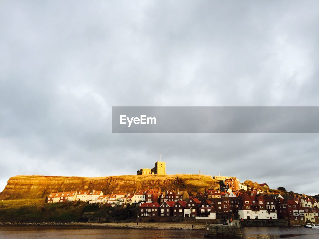Buildings By Mountain At Whitby Against Cloudy Sky