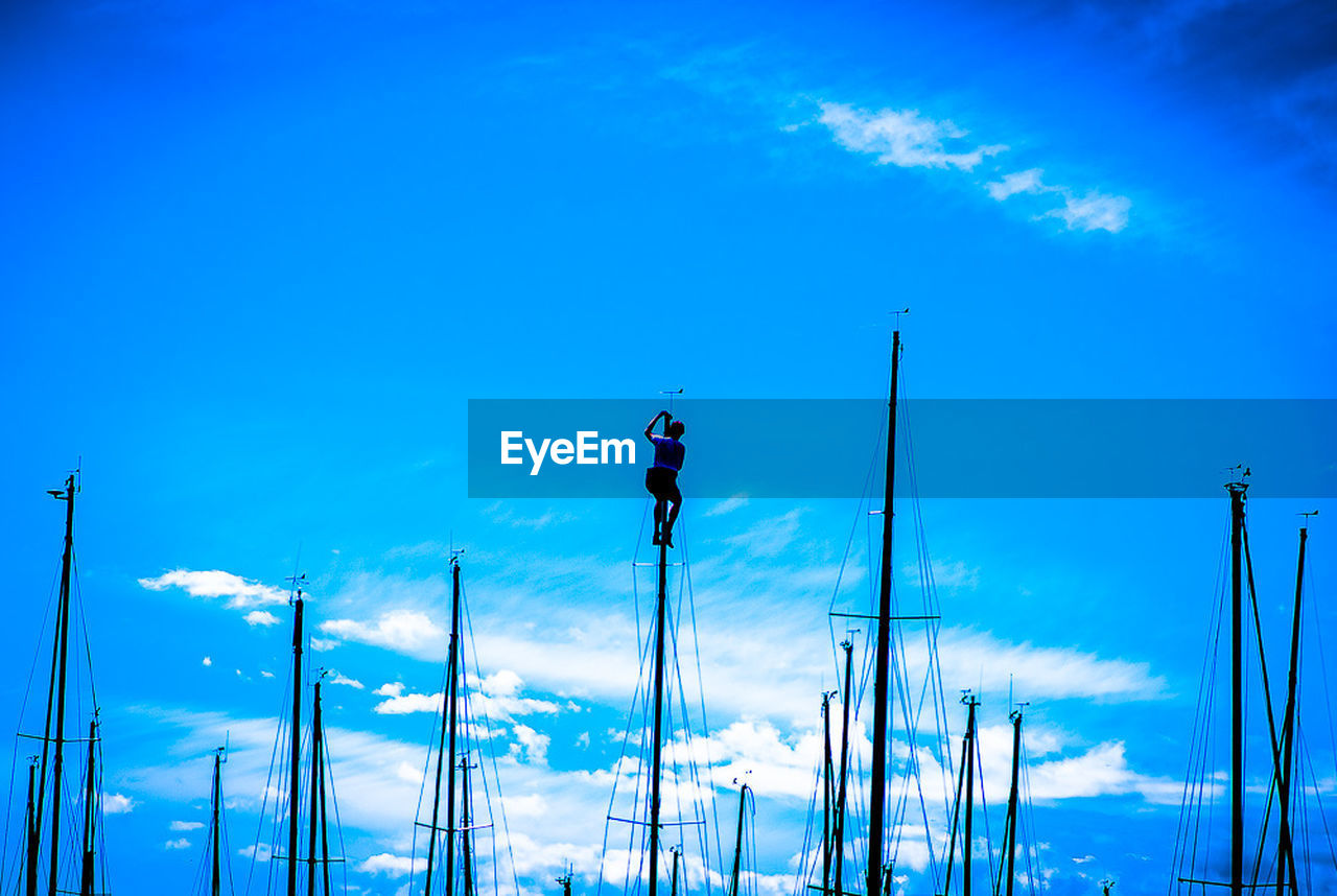 Low angle view of man on sailboat mast against blue sky