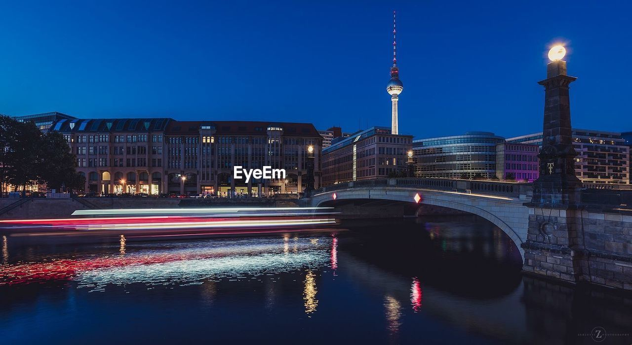 Light Trail On River By Fernsehturm Against Clear Sky At Dusk