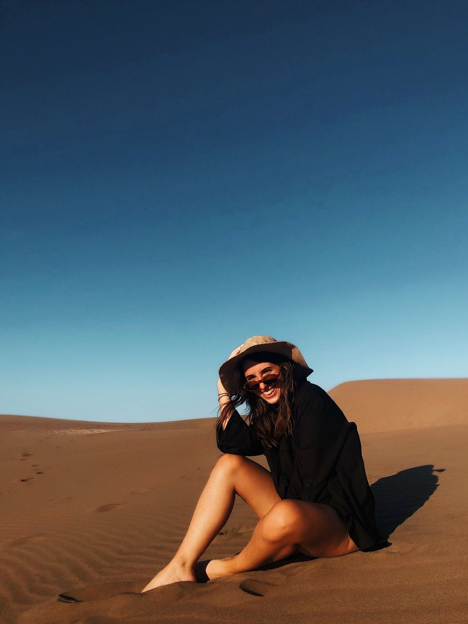 sky, land, desert, sand, one person, lifestyles, real people, sand dune, full length, young women, clear sky, leisure activity, young adult, landscape, copy space, nature, blue, sitting, sunlight, arid climate, climate, outdoors