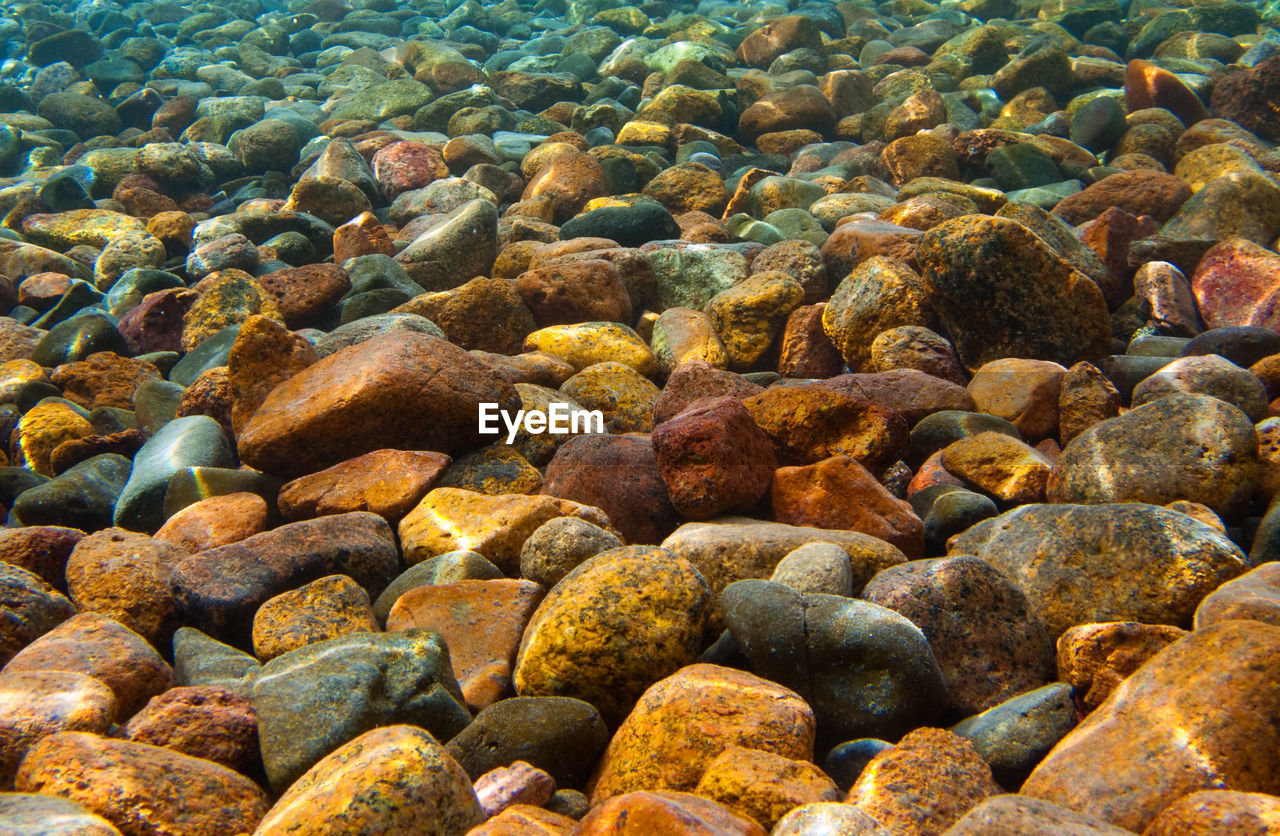 HIGH ANGLE VIEW OF PEBBLES ON SHORE