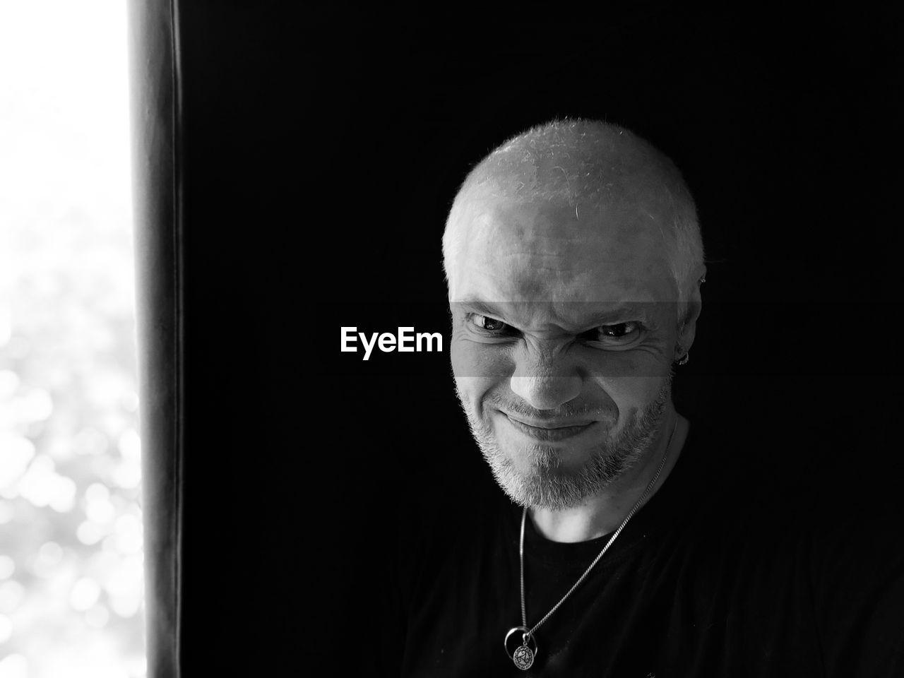 Close-Up Portrait Of Smiling Mature Man Making Face