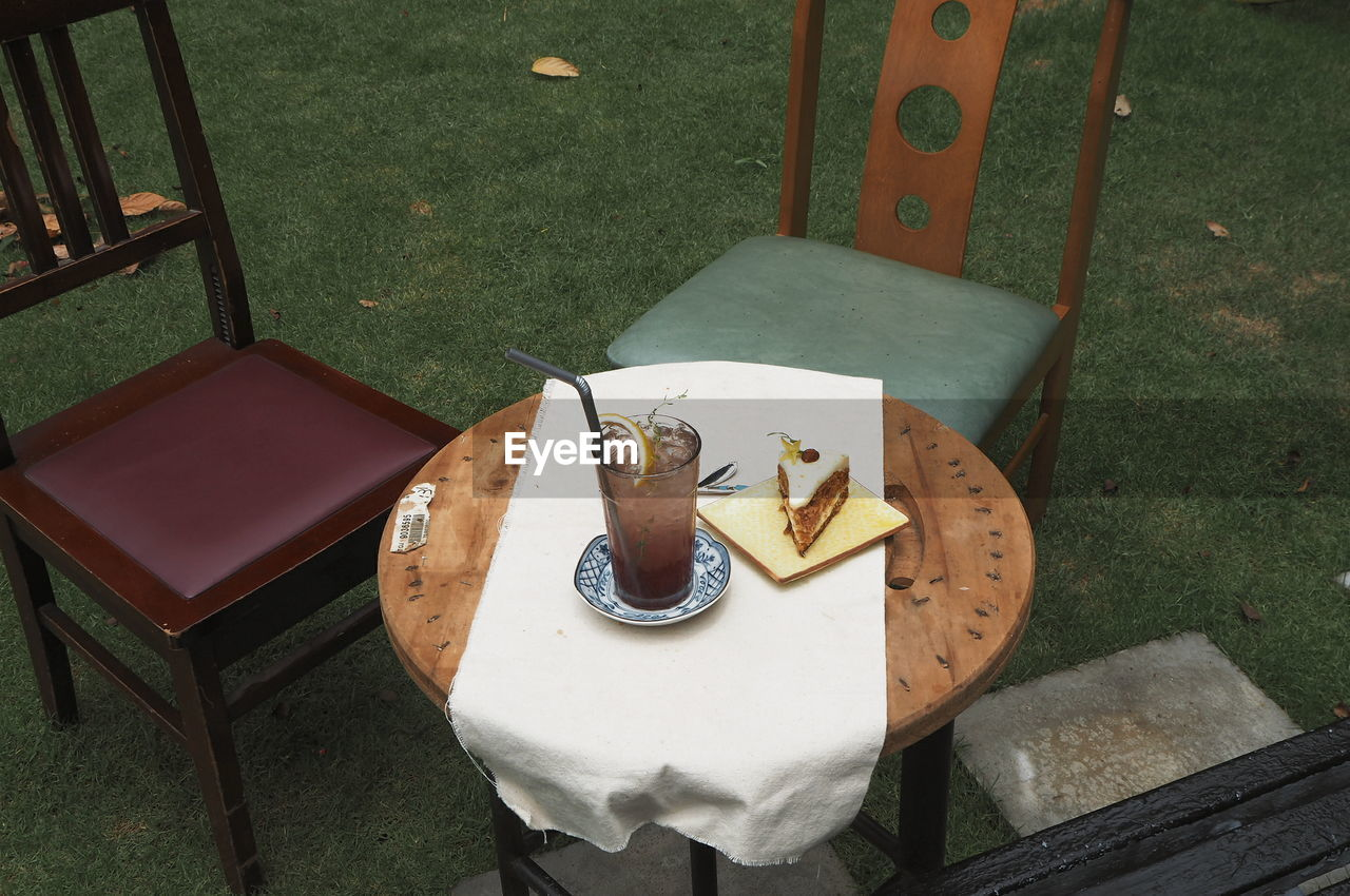 table, seat, high angle view, chair, no people, food and drink, animal, animal themes, day, food, plate, drink, absence, front or back yard, refreshment, freshness, representation, still life, nature, wood - material, outdoors