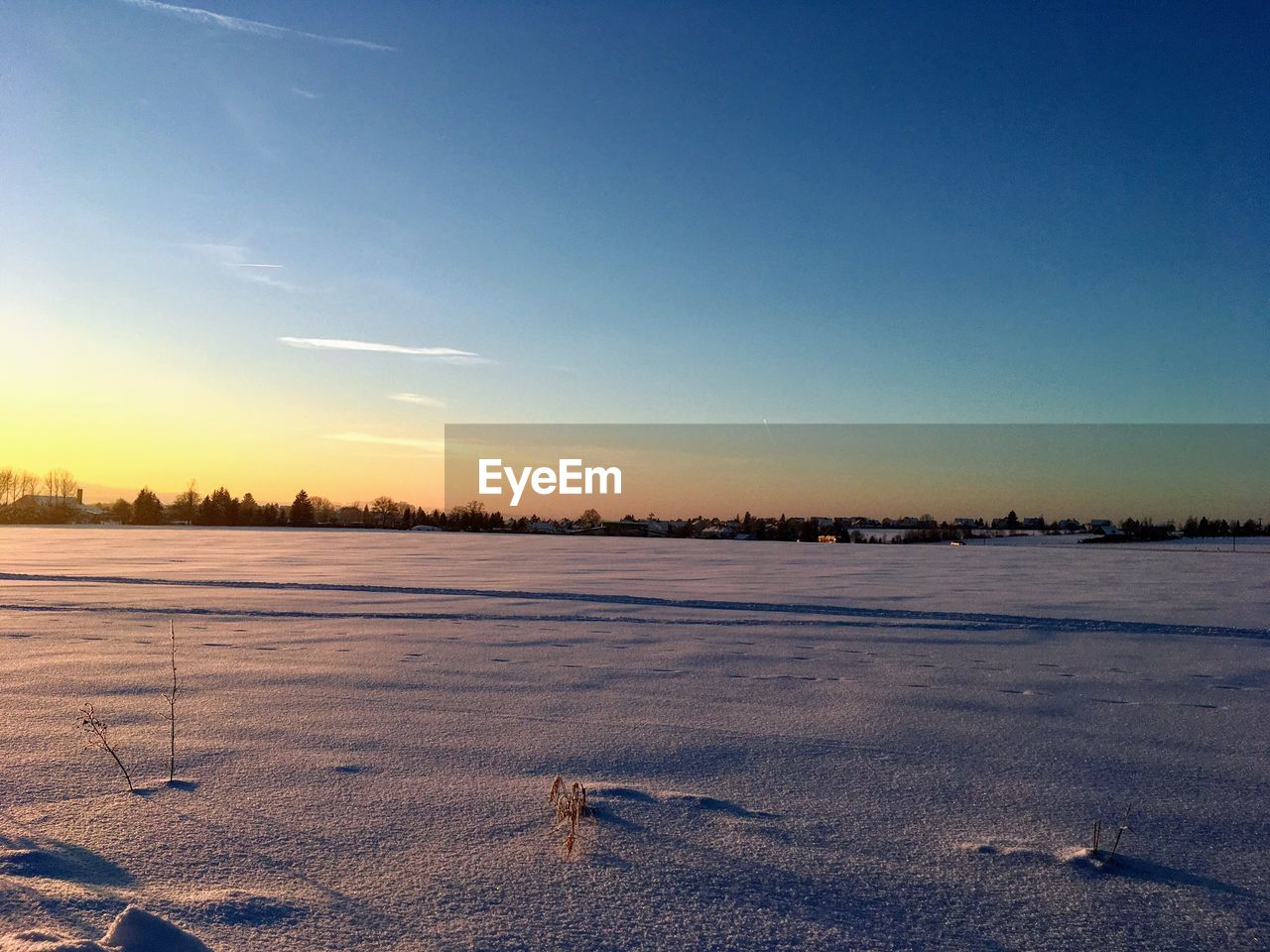 sky, snow, cold temperature, winter, nature, tranquility, tranquil scene, beauty in nature, no people, sunset, scenics - nature, environment, covering, field, landscape, outdoors, sunlight, blue, frozen