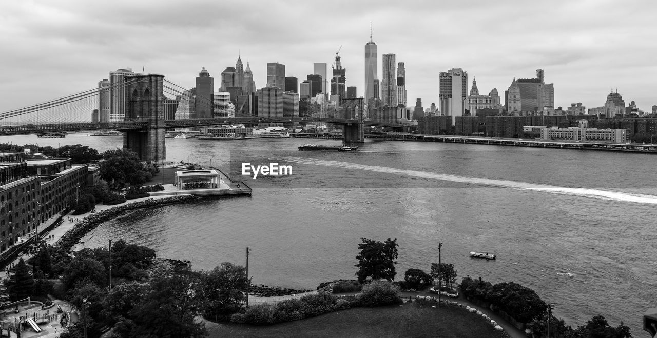 Brooklyn bridge over east river against sky in city