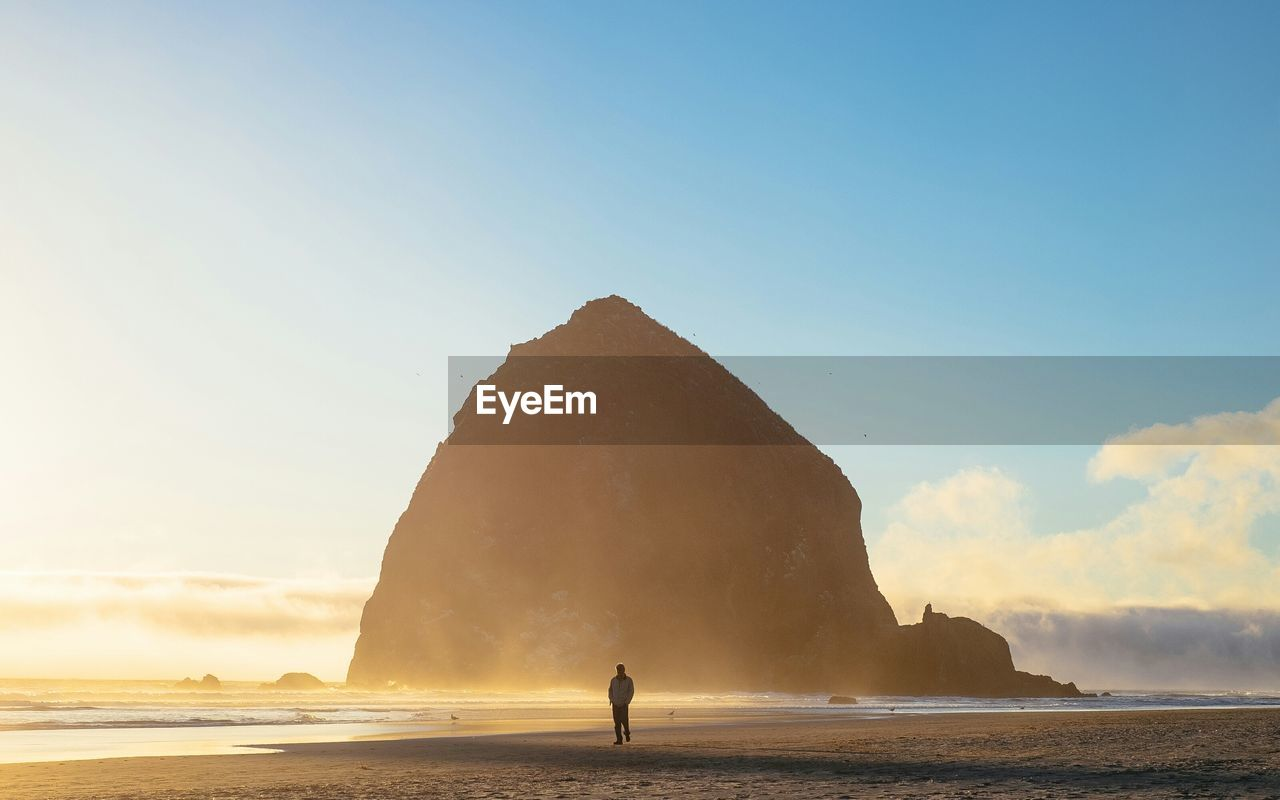 Man Walking At Beach Against Mountain And Sky During Sunrise