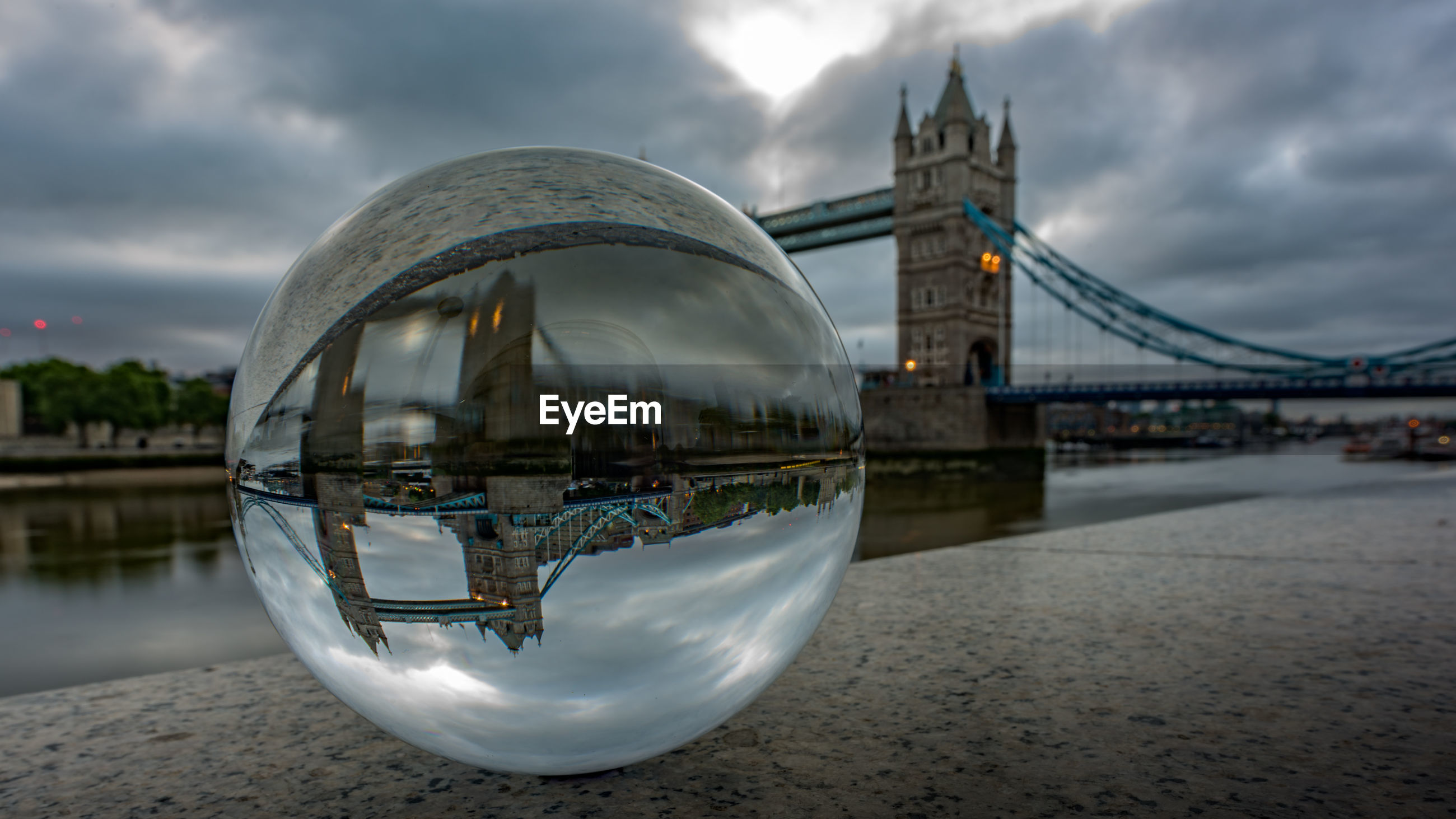 Reflection of london bridge on crystal ball at retaining wall against cloudy sky during sunset