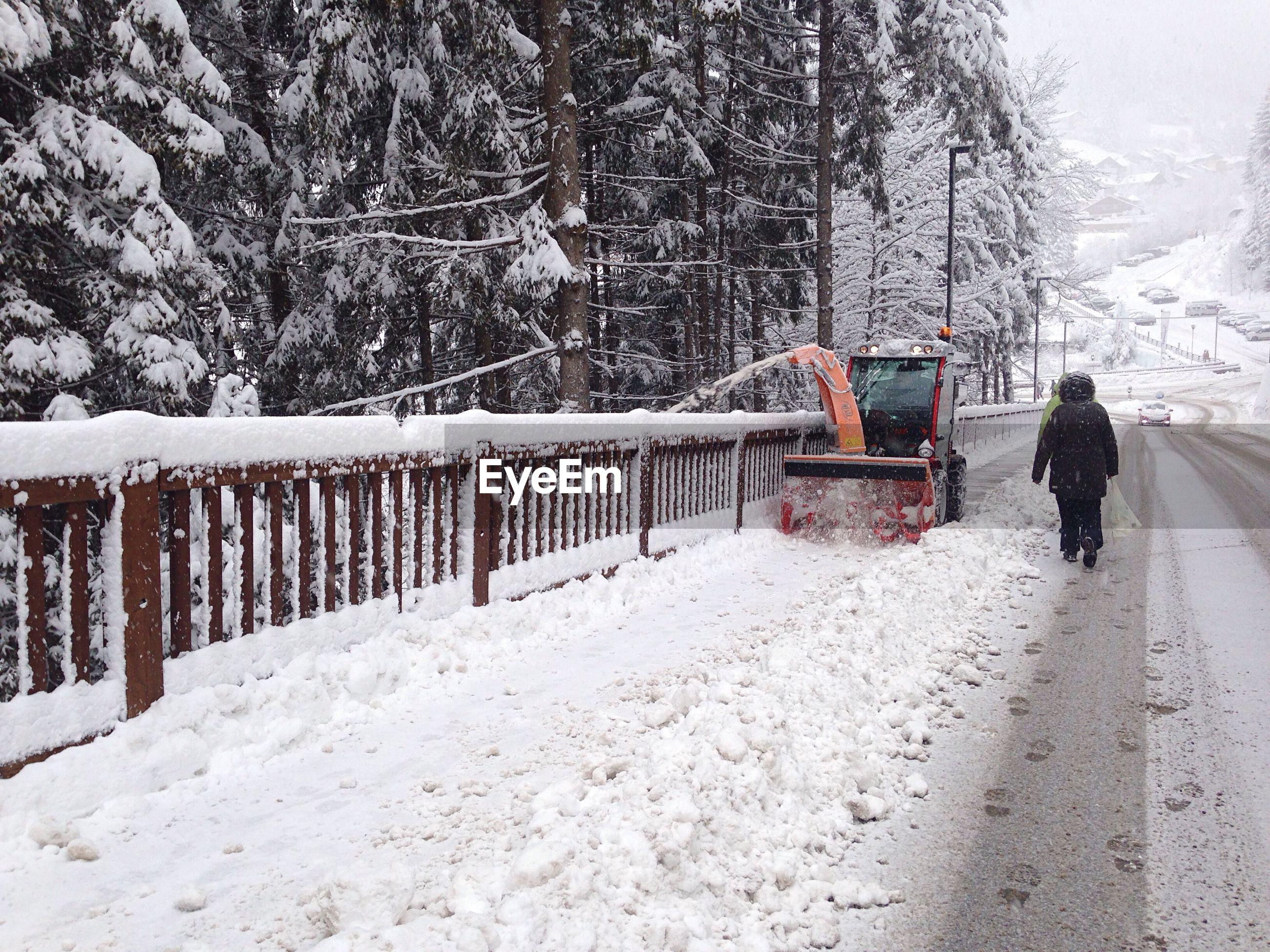 Snowplow by street during winter