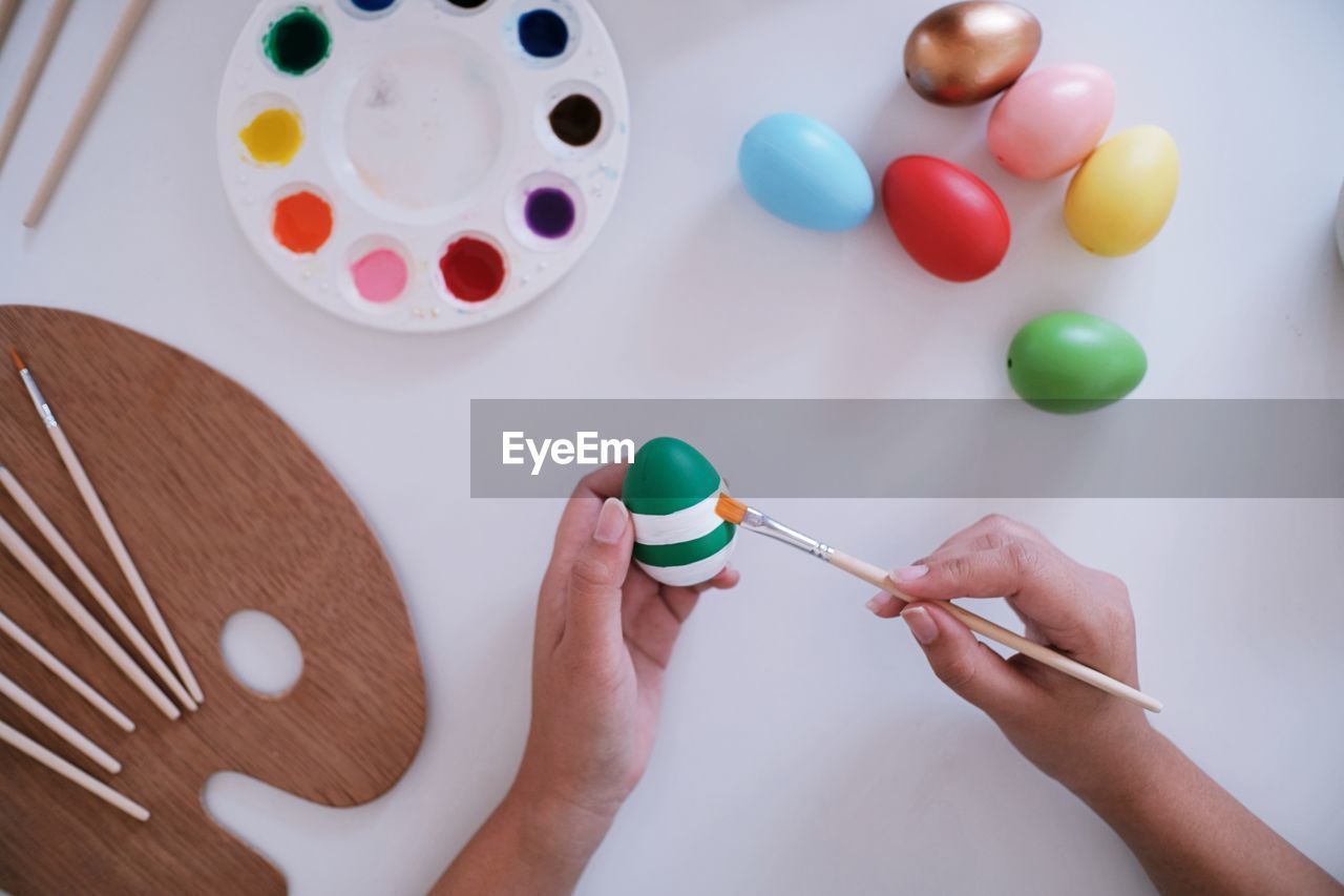 multi colored, holding, human hand, human body part, indoors, hand, real people, leisure activity, one person, table, paintbrush, brush, personal perspective, high angle view, paint, creativity, art and craft, body part, egg, celebration, watercolor paints, finger, art and craft equipment, human limb