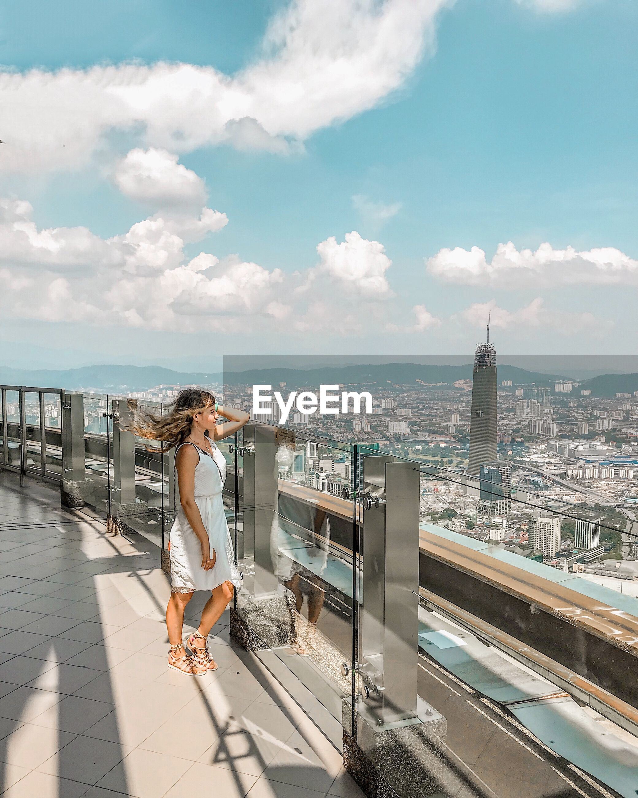 Side view of woman standing on balcony in city against sky