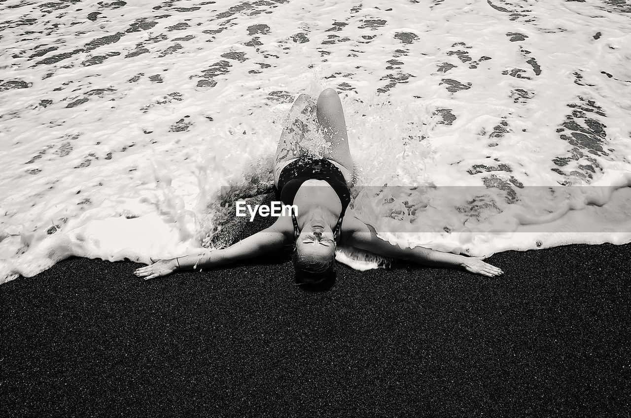 High Angle View Of Woman Lying On Shore At Beach