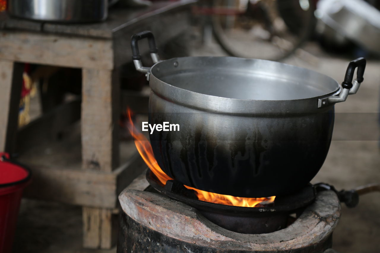 heat - temperature, kitchen utensil, burning, household equipment, stove, fire, fire - natural phenomenon, flame, preparation, kitchen, food and drink, appliance, cooking pan, indoors, domestic room, focus on foreground, container, no people, metal, food, wood burning stove, cooking utensil, preparing food, camping stove, saucepan