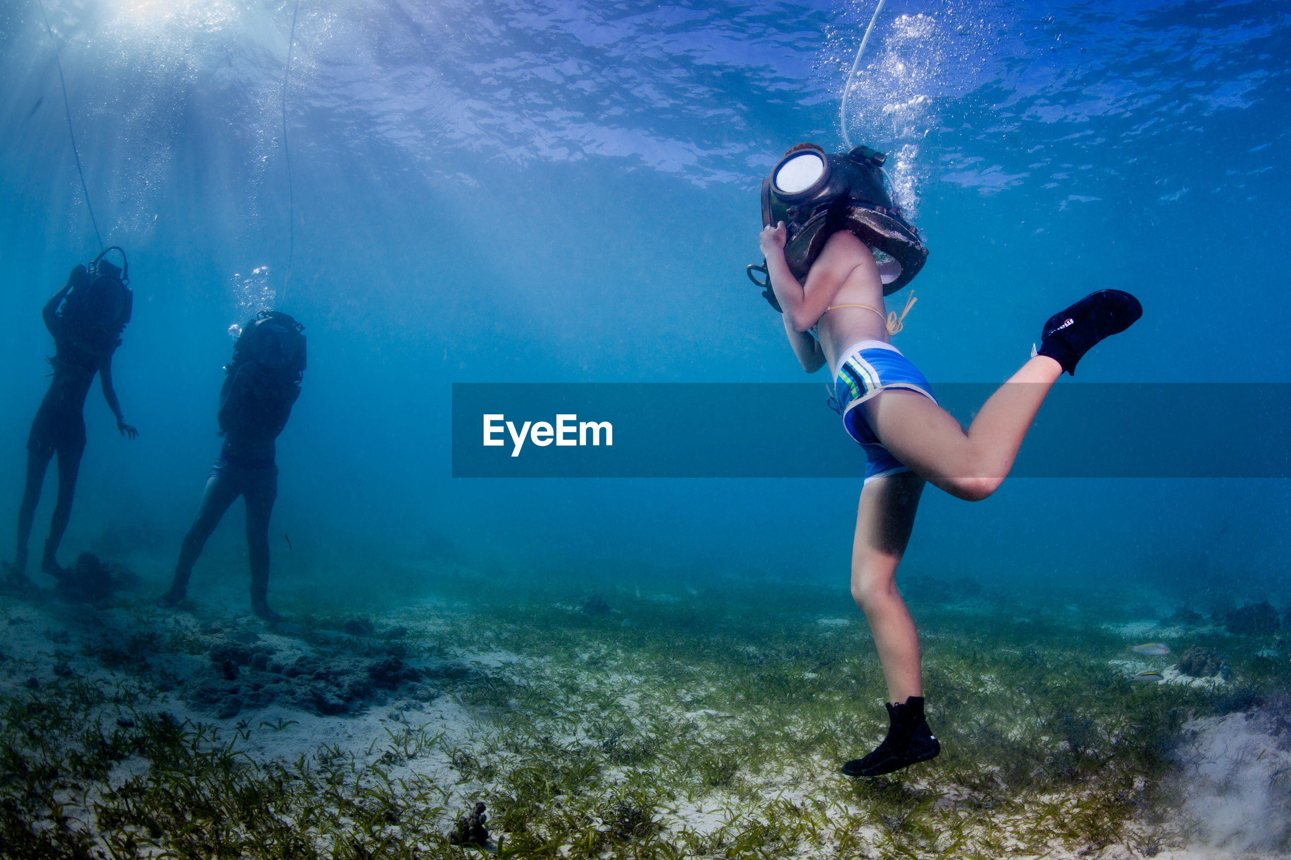 Three people standing undersea with diving equipment