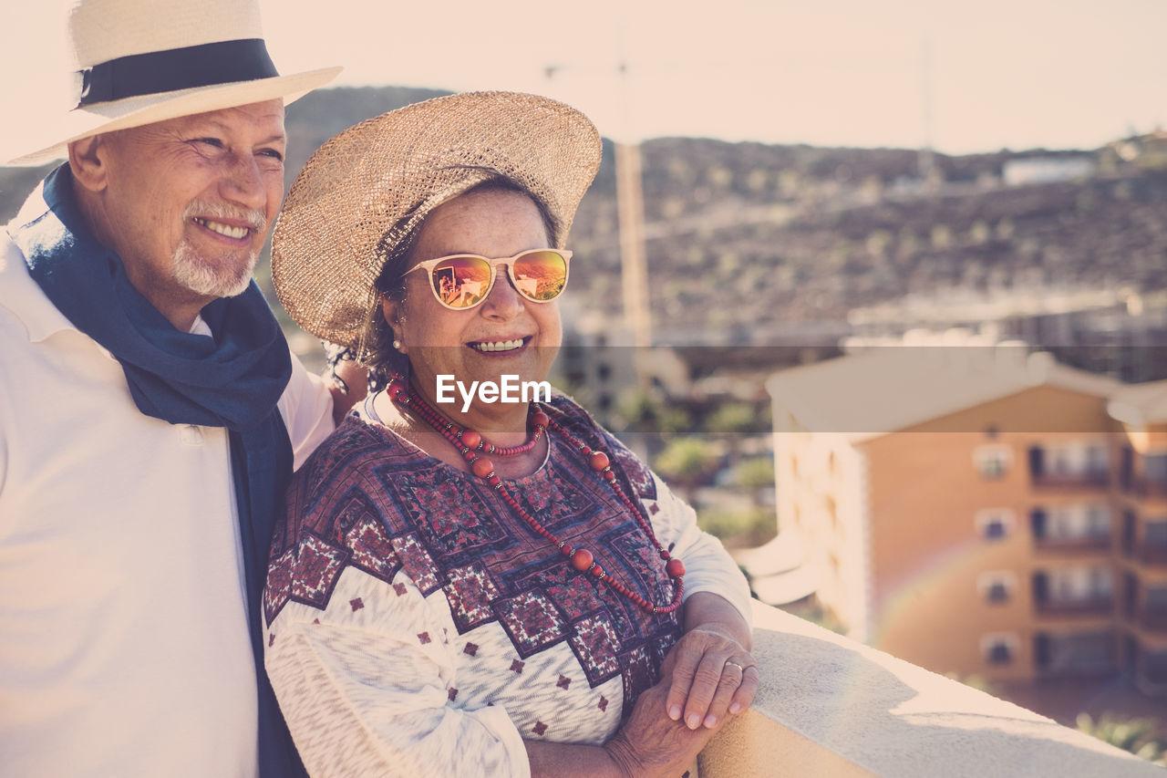 Smiling Senior Couple Standing On Building Terrace