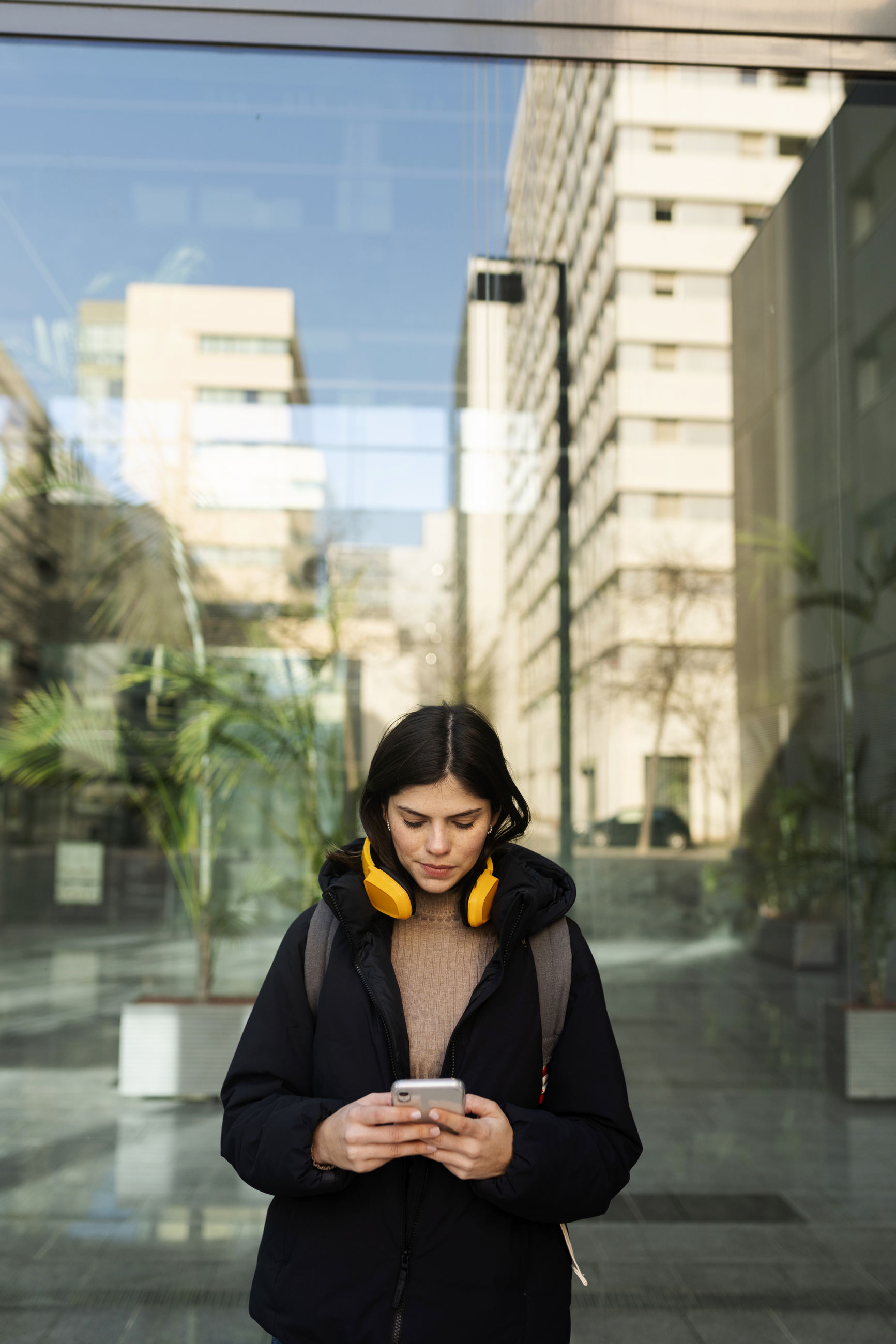 YOUNG WOMAN USING PHONE IN CITY