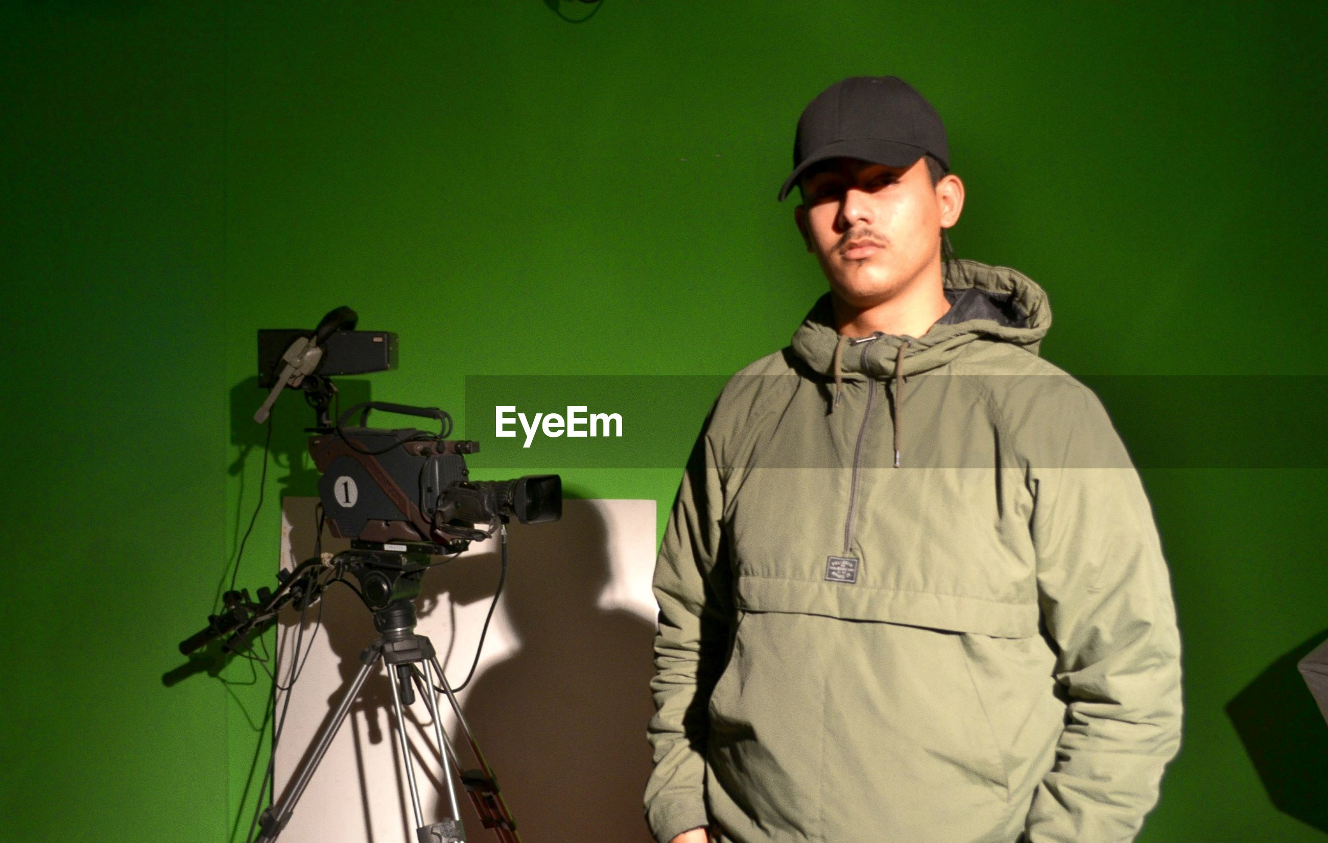 Portrait of man standing by movie camera against green wall