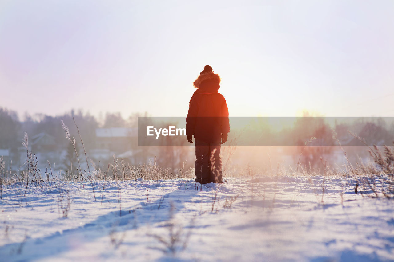 Man Standing On Snow Covered Landscape