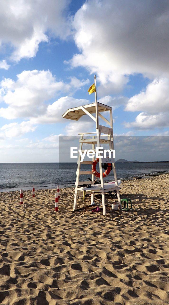 Lifeguard chair at beach against sky