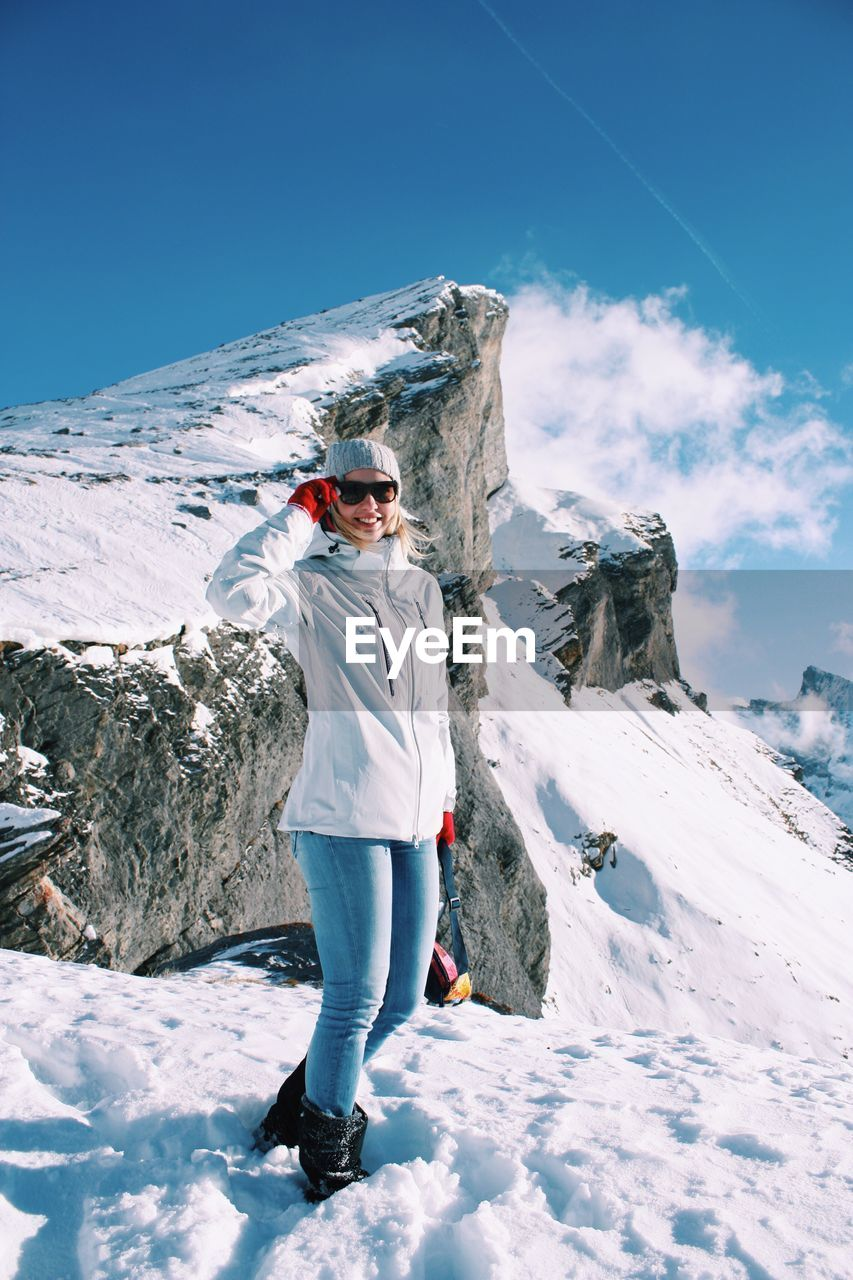 Full Length Of Woman Standing On Snowcapped Mountain