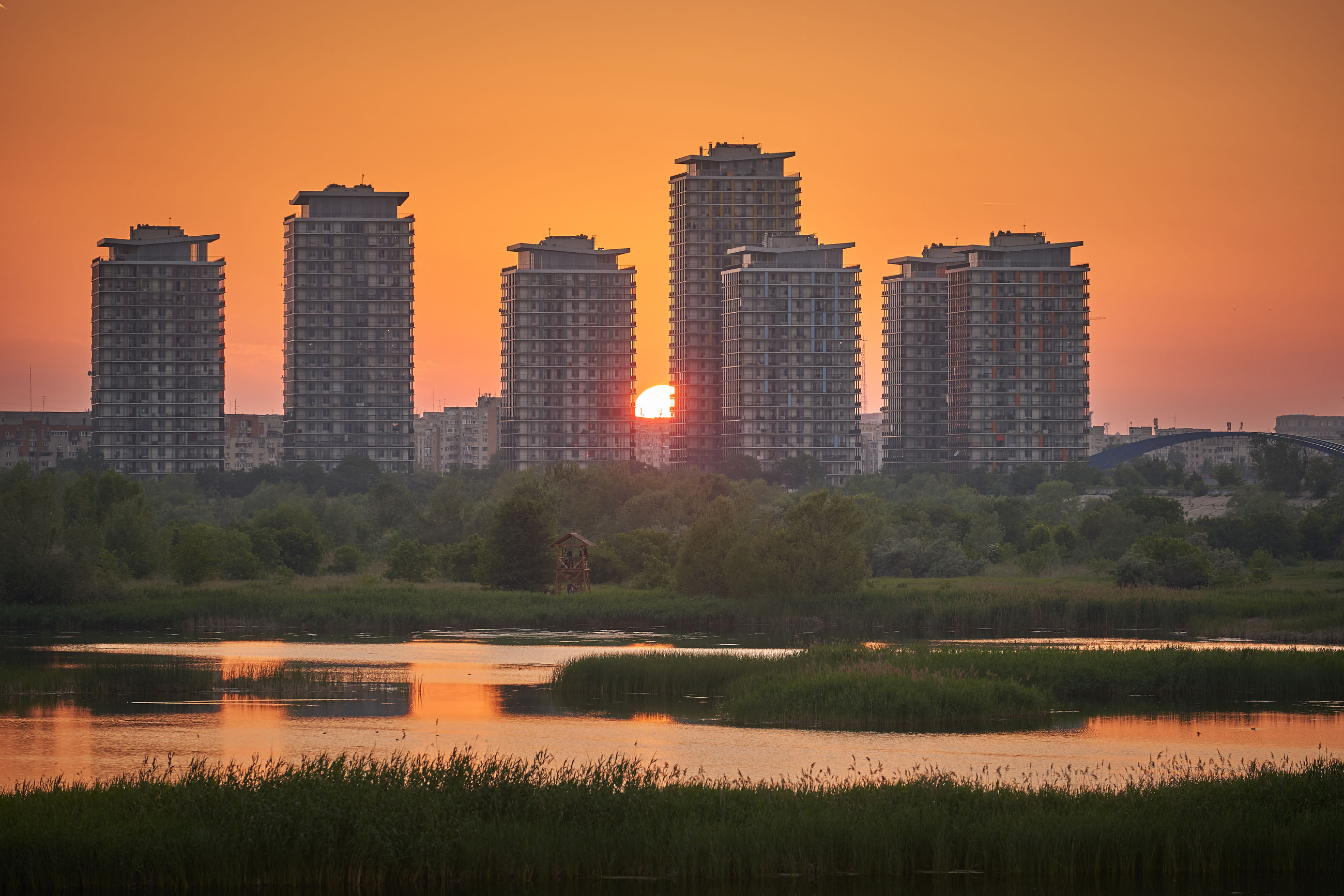 VIEW OF LAKE AND BUILDINGS AGAINST ORANGE SKY