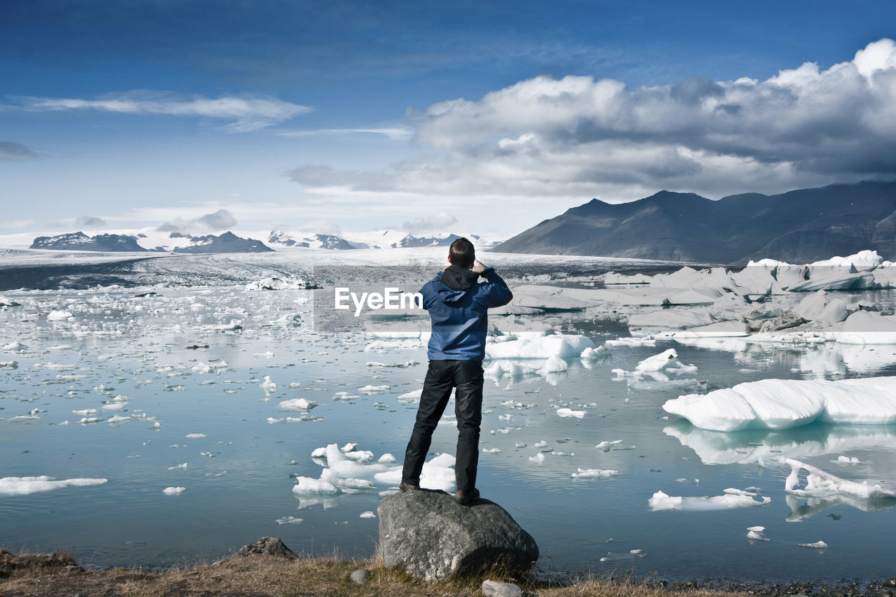 Man Standing In Front Of Glaciers Against Sky