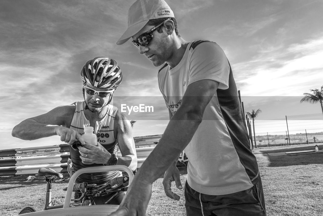 two people, sport, helmet, sports helmet, leisure activity, headwear, sky, competitive sport, sports clothing, outdoors, team sport, standing, men, lifestyles, stadium, day, real people, young adult, sportsman, adult, people
