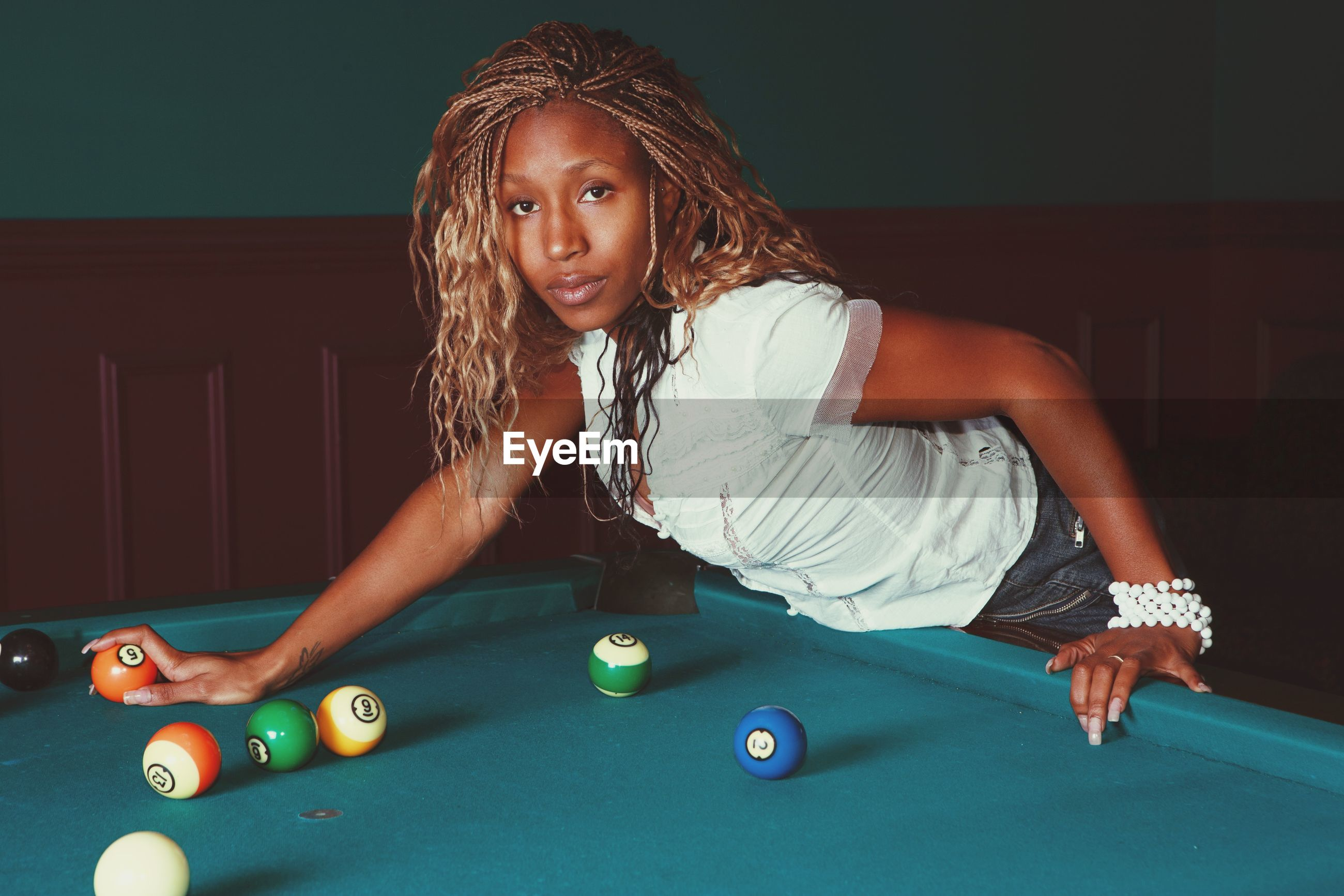 Portrait of woman standing by pool table