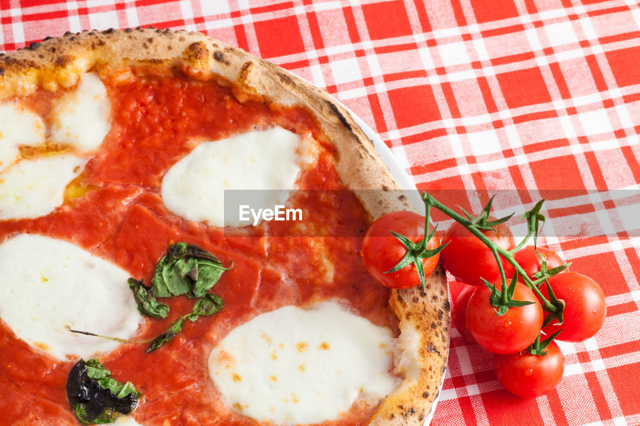 Close-up of tomatoes and pizza on table at home