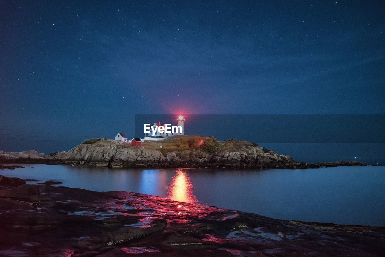 Reflection Of Illuminated Lighthouse In Water At Night
