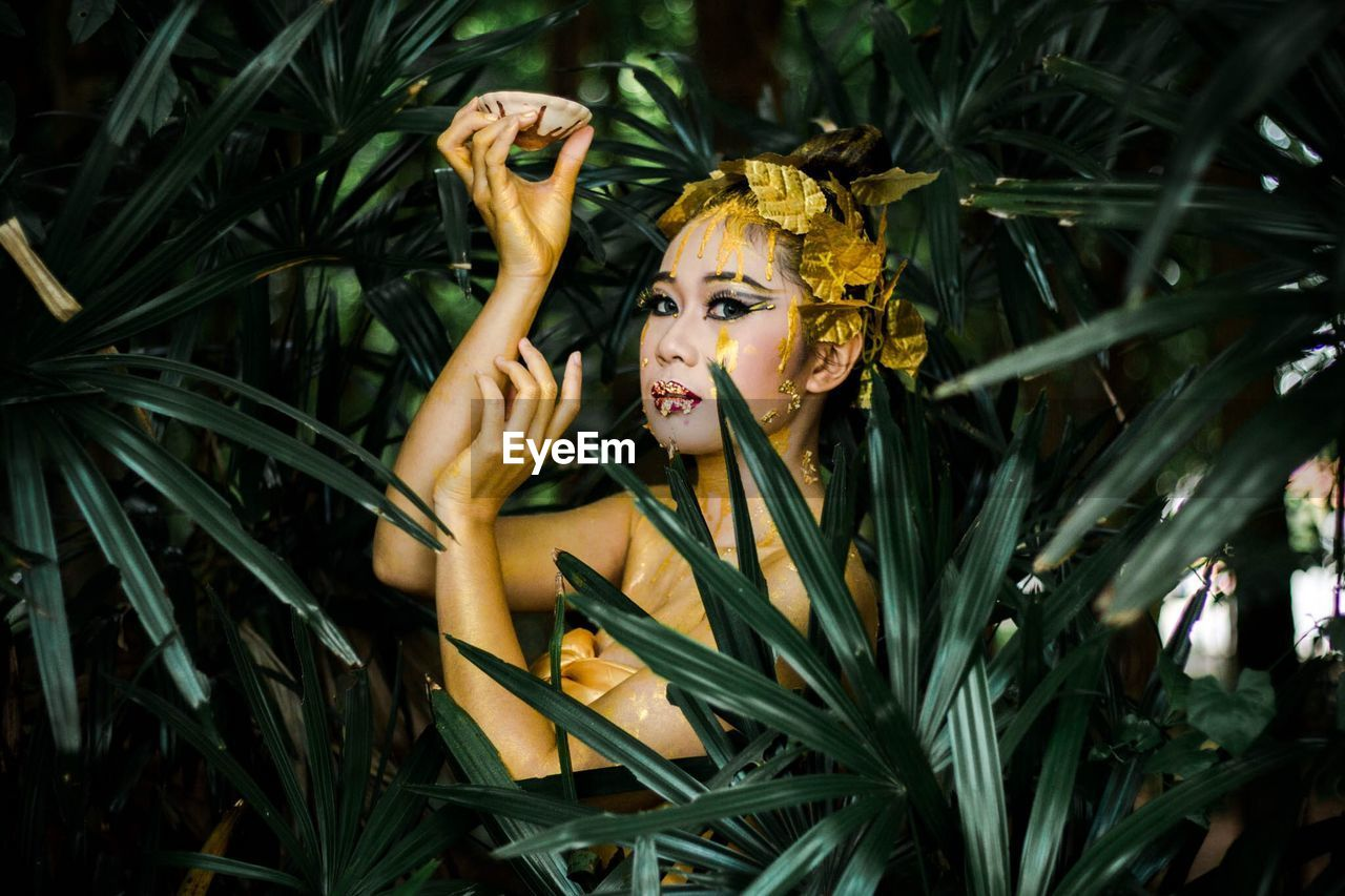 Portrait Of Young Woman With Face Paint Amidst Leaves