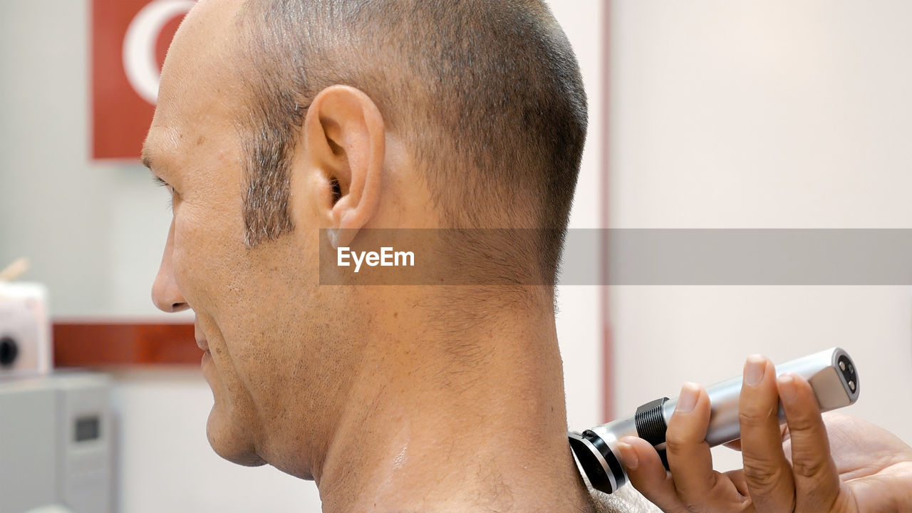 Barber Trimming Neck Hair Of Mature Man In Salon