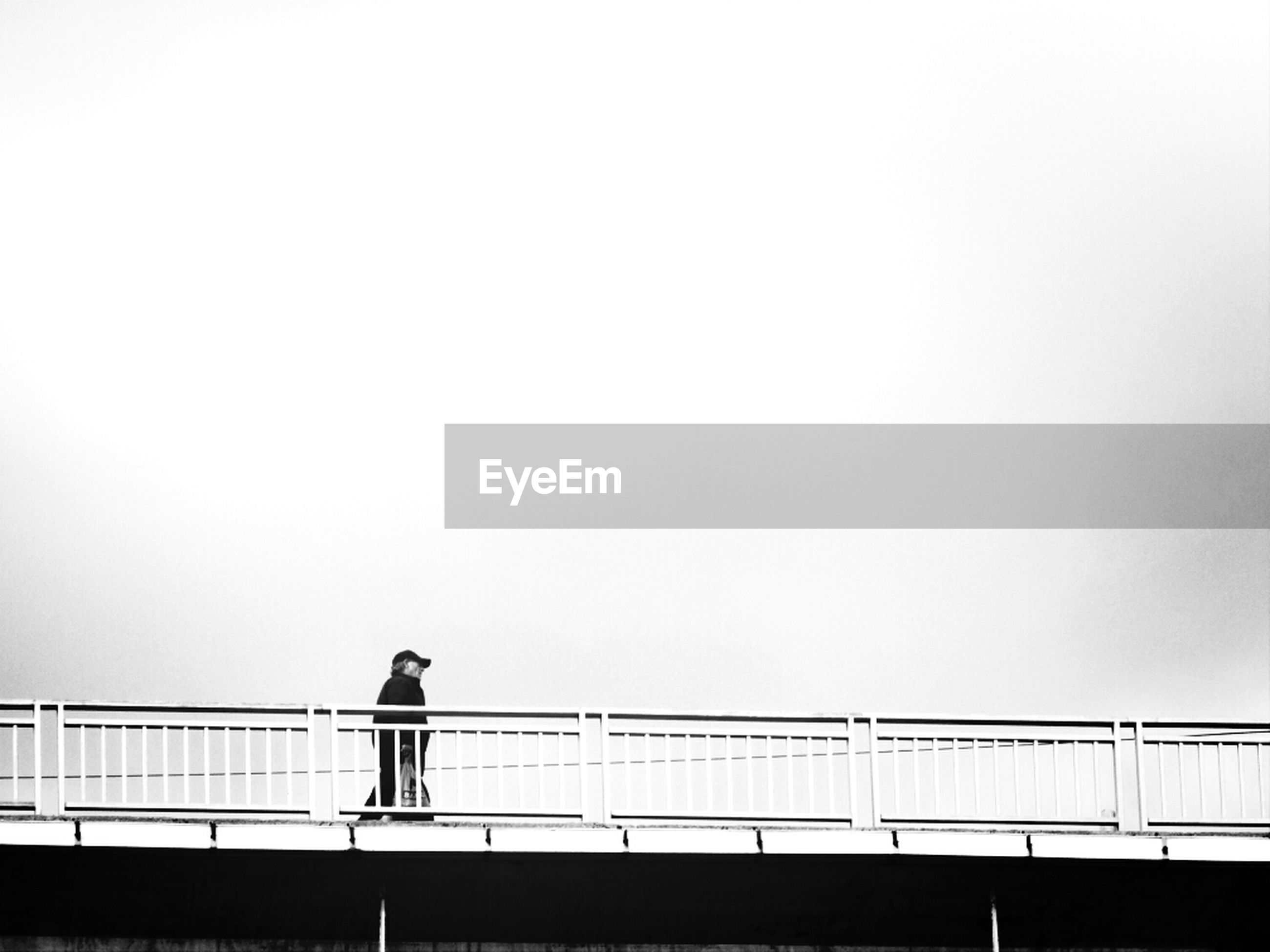 Man walking on bridge against clear sky