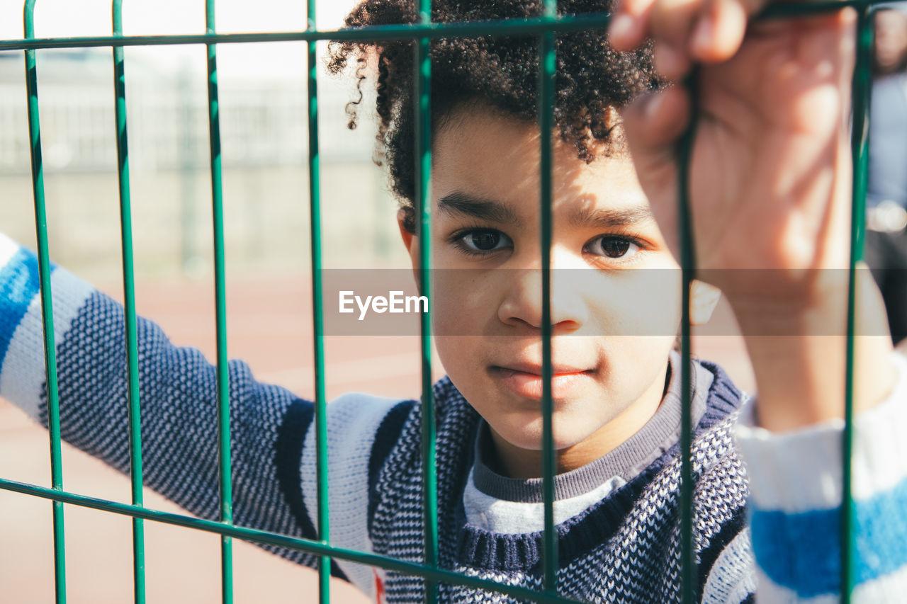 Portrait Of Cute Boy Seen Through Fence