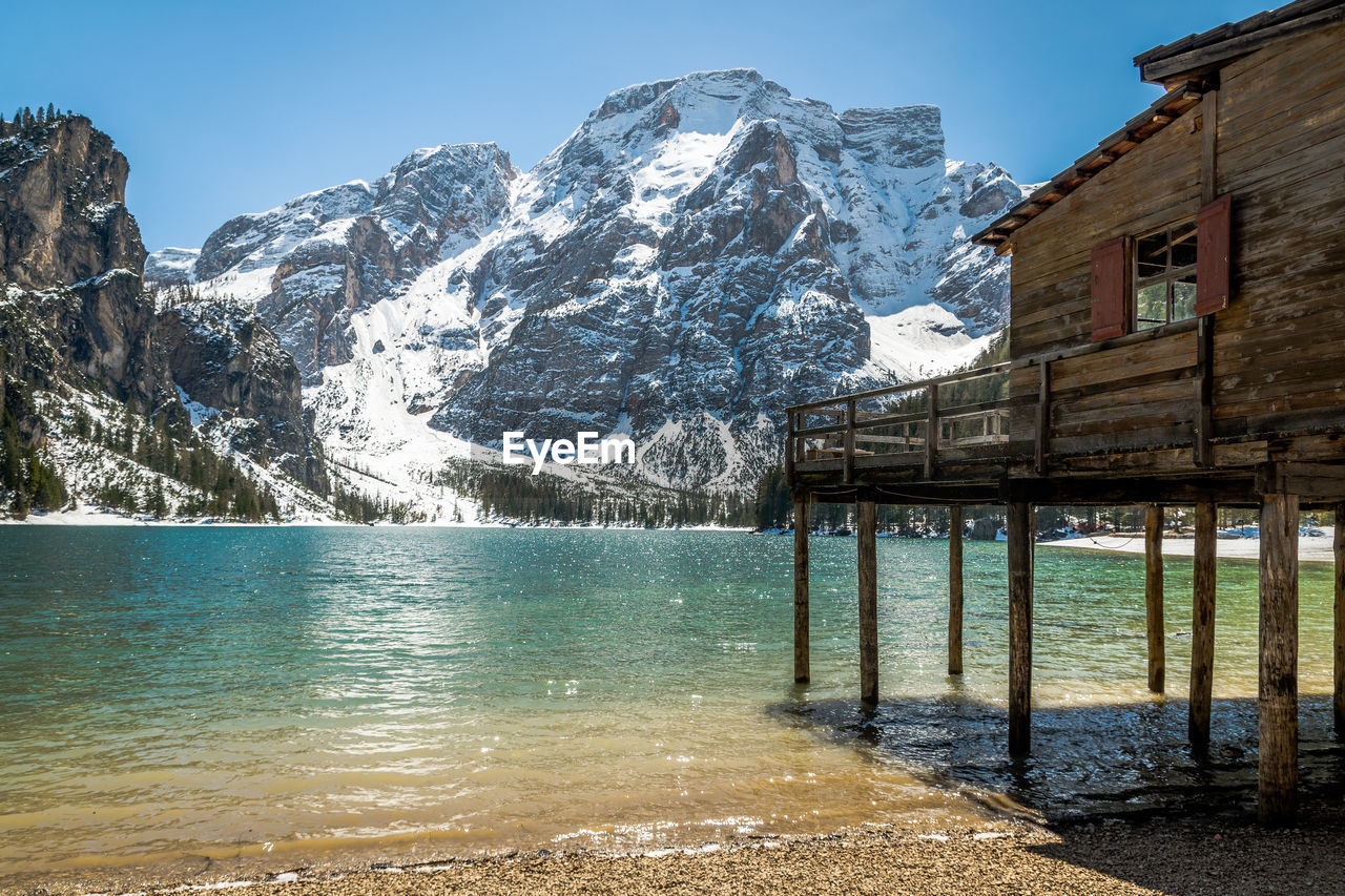 water, built structure, architecture, mountain, sky, beauty in nature, nature, building exterior, day, no people, scenics - nature, sunlight, clear sky, building, cold temperature, sea, outdoors, mountain range, snow, snowcapped mountain, mountain peak, turquoise colored