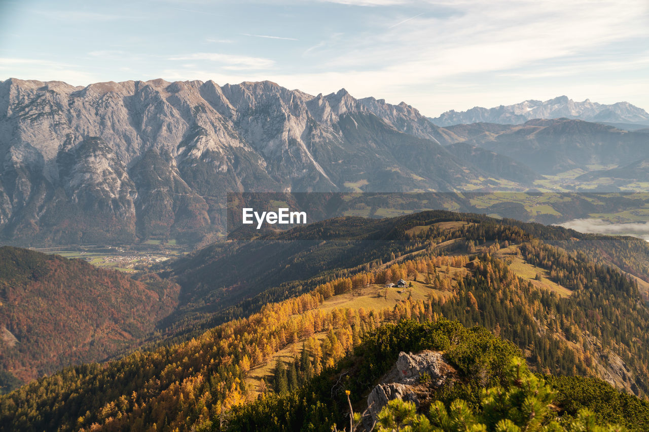 Panoramic view at mountain hut surrounded by fall colored larch trees, werfen in salzburg, austria.