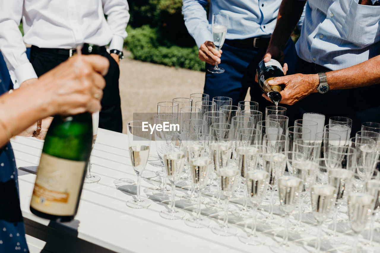Midsection of men standing by champagne at wedding ceremony
