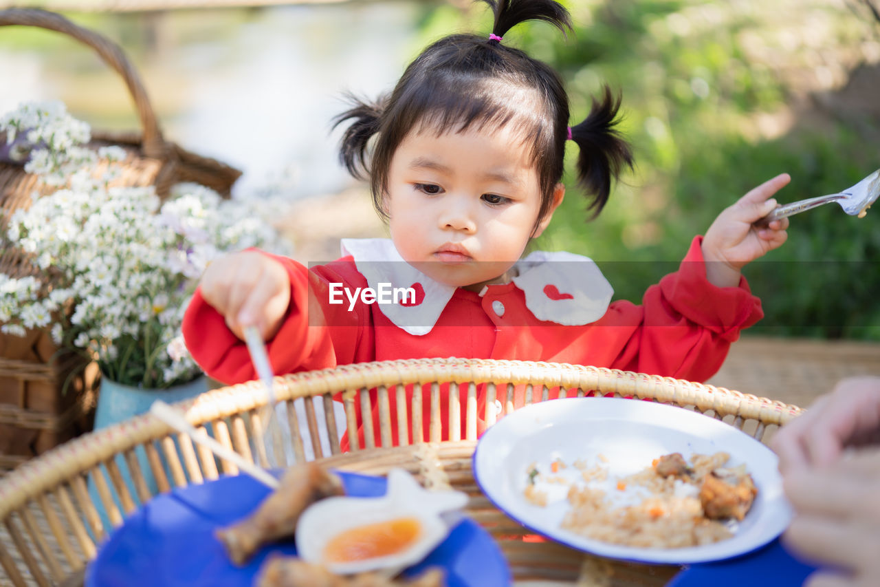 Cute girl eating food while sitting at park