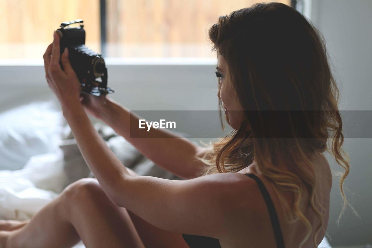 Woman Taking Selfie With Analog Camera