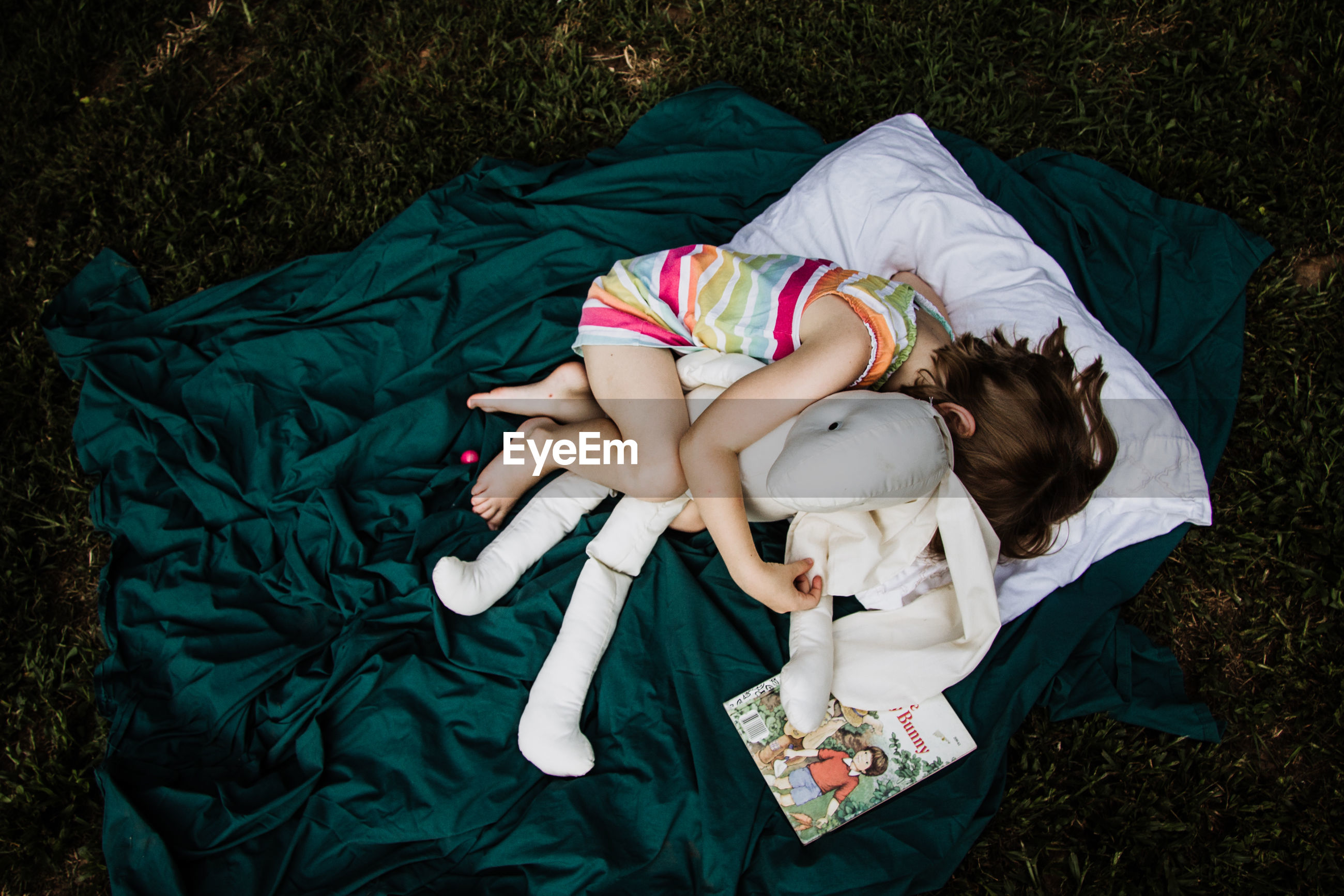 High angle view of girl with stuffed toy lying on blanket