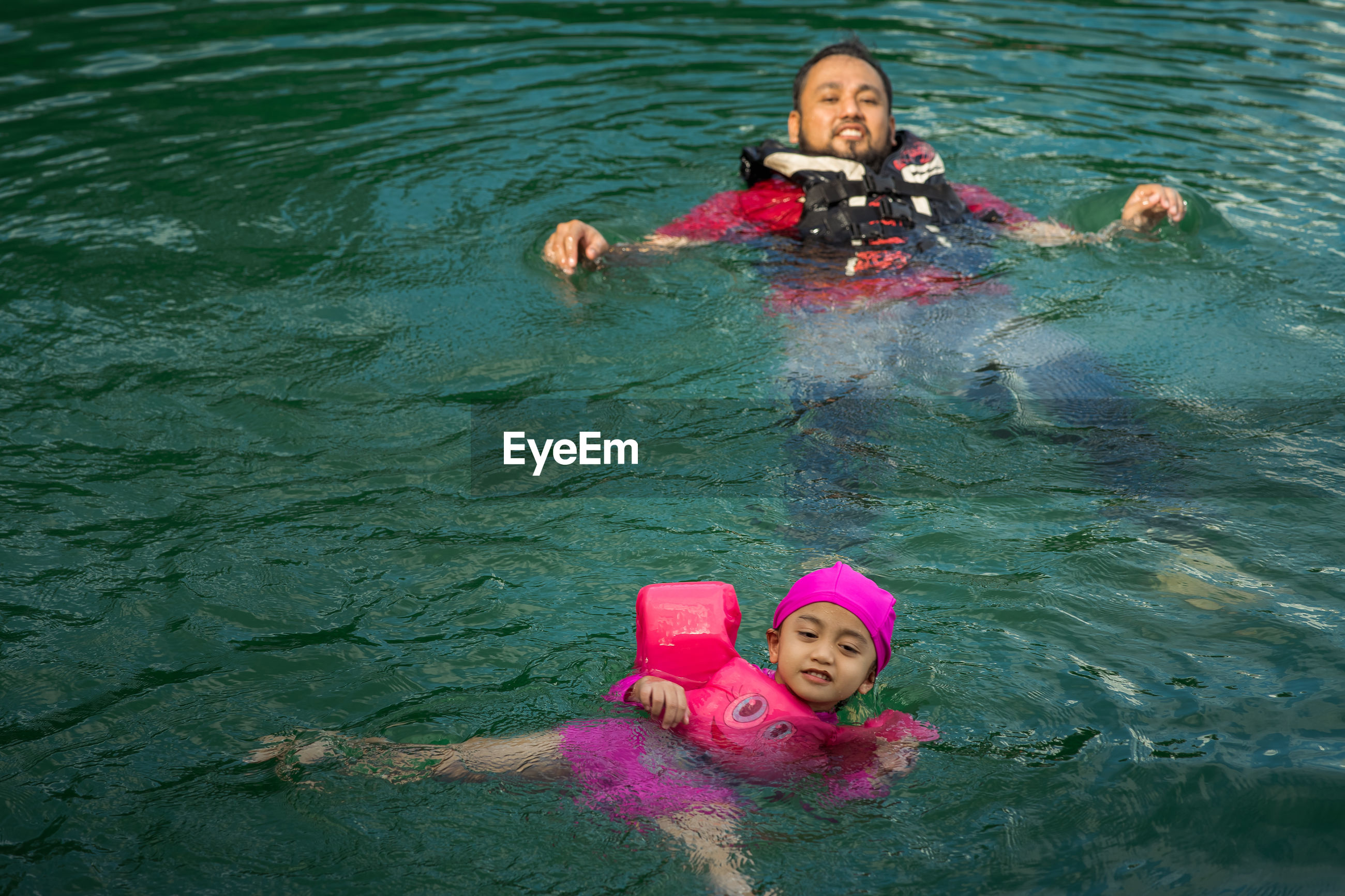 High angle view of father and daughter swimming in lake