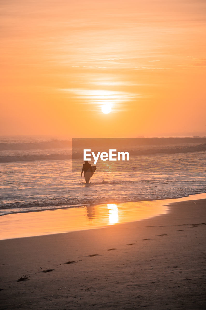 Surfer Standing In Sea During Sunset