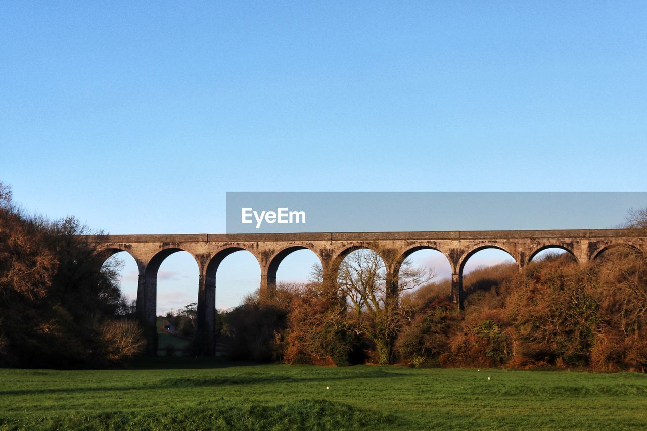 arch, bridge - man made structure, viaduct, connection, clear sky, copy space, architecture, day, no people, nature, transportation, built structure, landscape, grass, outdoors, tree, sky